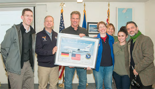 Ambassador Brown receiving a signed lithograph with a flag that was flown on SOFIA